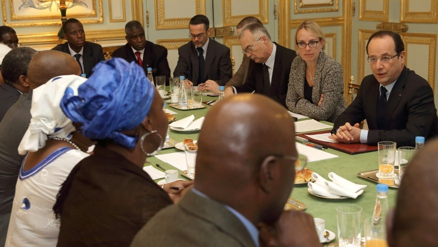 Jan. 13, 2013: French President Francois Hollande, right, speaks with members of Malian associations in France during a meeting at the Elysee Palace in Paris.