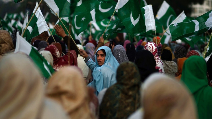 Jan. 14, 2013 - Supporters of Pakistani Sunni Muslim cleric Tahir-ul-Qadri, wave their national flag and chant slogans, while waiting his arrival to Islamabad, Pakistan.