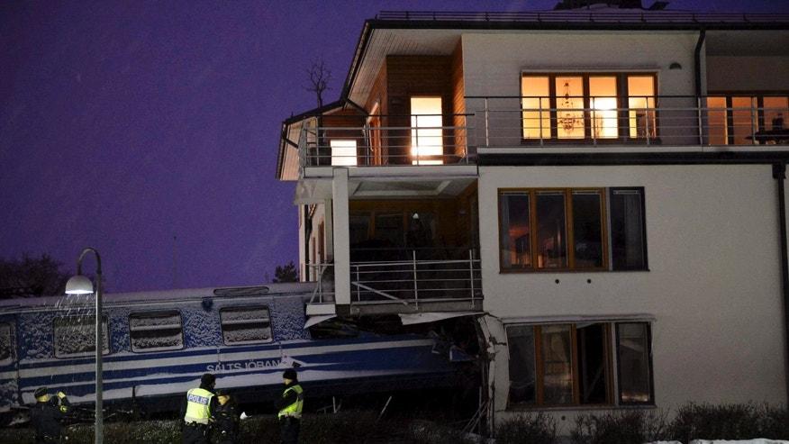 Emergency services attend the scene after a  derailed train crashed into the side of a  residential building in Saltsjöbaden outside Stockholm, Tuesday  Jan, 15, 2013. A woman obtained the keys to the train and drove it away before it crashed into the building. The woman was injured in the incident and there are no reports of injuries of people in the building . (AP Photo/Jonas Ekströmer) **  SWEDEN OUT  **