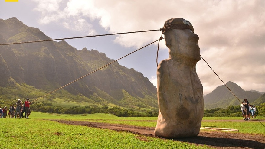 "A 10-foot, 5-ton replica of an Easter Island ""moai"" dances down the road, guided by teams on each side and behind it. Archaeologists Carl Lipo and Terry Hunt, who led the experiment, report that once the balance of the teams and ropes was established, the statue ""just did its thing."" The experiment, funded by the National Geographic Society, is described in the July 2012 issue of National Geographic magazine."