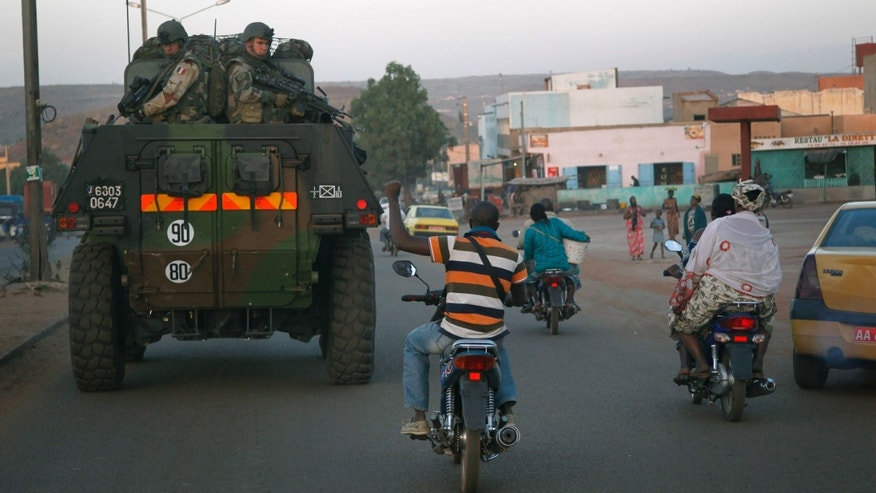 A motorcyclist waves his support as French troops in two armored personnel carriers drive through Mali's capital Bamako on the road to Mopti Tuesday Jan. 15, 2013. French forces led an all-night aerial bombing campaign Tuesday to wrest control of a small Malian town from armed Islamist extremists who seized the area, including its strategic military camp. A a convoy of 40 to 50 trucks carrying French troops crossed into Mali from Ivory Coast as France prepares for a possible land assault. Several thousand soldiers from the nations neighboring Mali are also expected to begin arriving in coming days. (AP Photo/Jerome Delay)