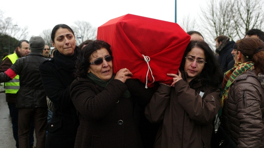 Kurdish people carry the coffin of one of the three activists during a memorial ceremony, in Villiers le Bel, north of Paris, Tuesday, Jan. 15, 2013, before their bodies are sent to Turkey for burial. Three Kurdish women were shot dead at a pro-Kurdish center in Paris on Thursday Jan. 10, in what the French interior minister called an execution. (AP Photo/Thibault Camus)