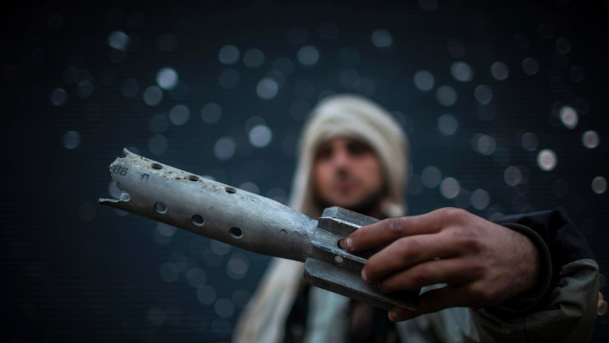 A Free Syrian Army fighter displays a damaged ordinance in Aleppo, Syria, Tuesday, Jan. 15, 2013. Two explosions struck the main university in the northern Syrian city of Aleppo on Tuesday, causing an unknown number of casualties, state media and anti-government activists said. (AP Photo/Andoni Lubaki)