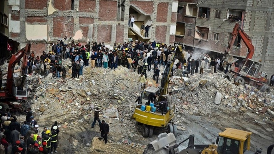 Jan. 16, 2013: Egyptians stand in rubble after an eight story building collapsed in Alexandria, Egypt.