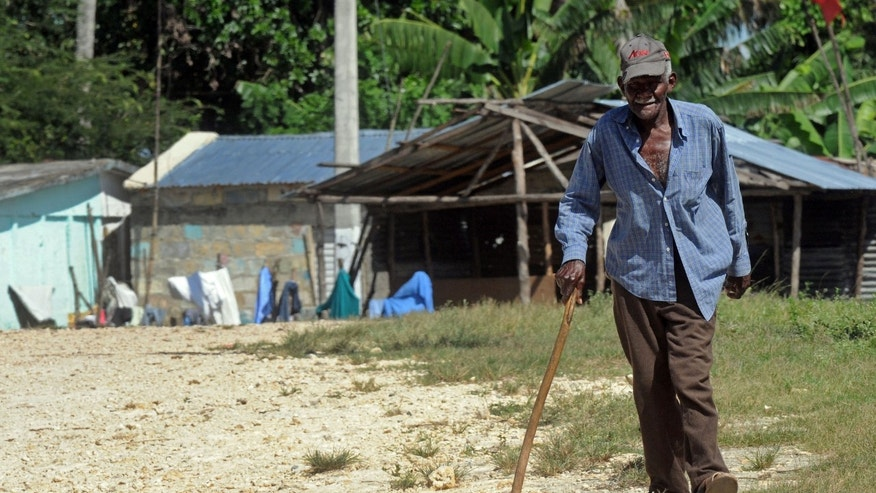 In this Oct. 5, 2012 photo, Haitian immigrant Julien Henrique, 92, strolls through a sugars workers community with the aid of a stick in San Pedro de Macoris, Dominican Republic. Henrique, who spent 50 years working in the sugar cane fields of the Dominican Republic, was unable to collect a monthly pension after he left the company because he didn't have a passport and birth certificate. Recently Henrique was able to obtain a Haitian passport as part of a program sponsored by the Office of the U.N. Commissioner for Refugees to provide identity documents to Haitian immigrants in the Dominican Republic. (AP Photo/Manuel Diaz)