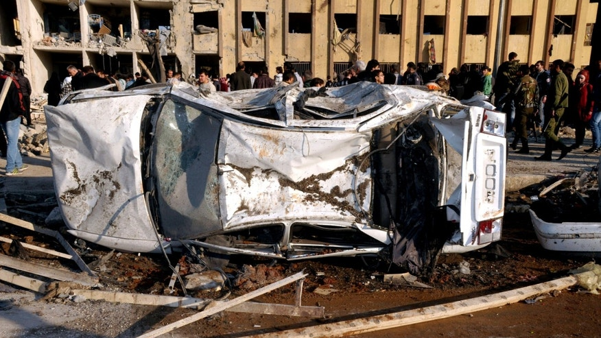 In this photo released by the Syrian official news agency SANA, Syrian people gather at the site after an explosion hit a university in Aleppo, Syria, Tuesday, Jan. 15, 2013. Two explosions struck the main university in the northern Syrian city of Aleppo on Tuesday, causing an unknown number of casualties, state media and anti-government activists said. There were conflicting reports as to what caused the blast at Aleppo University, which was in session Tuesday. (AP Photo/SANA)