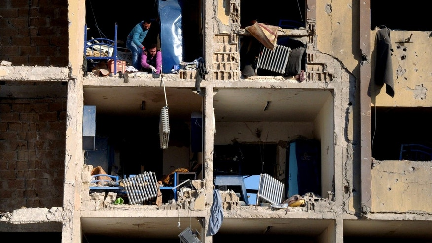 In this photo released by the Syrian official news agency SANA, Syrians stand in rubble of the damaged university building caused by an explosion in Aleppo, Syria, Tuesday, Jan. 15, 2013. Two explosions struck the main university in the northern Syrian city of Aleppo on Tuesday, causing an unknown number of casualties, state media and anti-government activists said. There were conflicting reports as to what caused the blast at Aleppo University, which was in session Tuesday. (AP Photo/SANA)