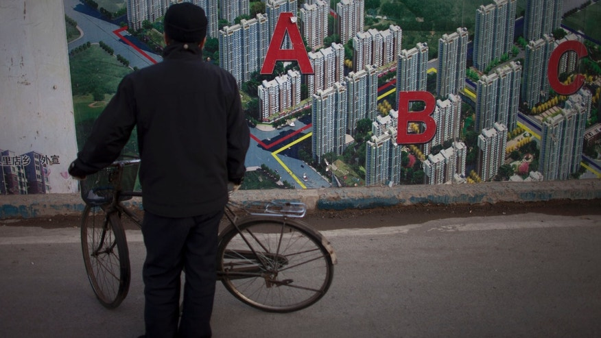 In this Jan. 17, 2013 photo, a man stops his bicycle to check an artistic rendering of a residential real estate project outside its construction site in Beijing, China, Thursday, Jan. 17, 2013.  China's economy rebounded in the final quarter of 2012 but optimism was tempered by warnings the shaky recovery could be vulnerable to a possible downturn in global trade. Economic growth rose to 7.9 percent in the three months ending in December as a recovery from China's deepest slowdown since the 2008 global crisis took hold, data showed Friday. (AP Photo/Alexander F. Yuan)