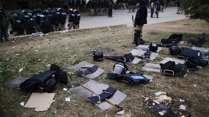 Pakistani riot police stand guard, to block supporters of Pakistani Sunni Muslim cleric Tahir-ul-Qadri from entering the high security area Red Zone, who are camping near the parliament, during an anti-government rally in Islamabad, Pakistan, Thursday, Jan. 17, 2013. Pakistan's anti-corruption chief refused a Supreme Court order to arrest the prime minister in a graft case Thursday citing a lack of evidence, in the latest clash between the government and the country's top court. The arrest order issued Tuesday intensified the sense of political crisis in Pakistan, where a firebrand Muslim cleric has been leading thousands in an anti-government protest in the heart of the capital, Islamabad, for the past four days. (AP Photo/Muhammed Muheisen)