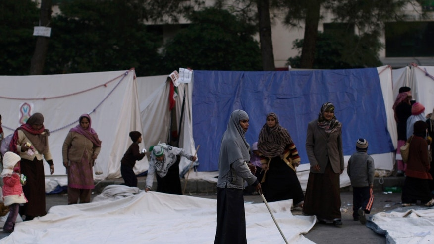 A supporter of Pakistani Sunni Muslim cleric Tahir-ul-Qadri, cleans the ground in front of the tents where she and others are camping near the parliament, during an anti-government rally in Islamabad, Pakistan, Thursday, Jan. 17, 2013. Pakistan's anti-corruption chief refused a Supreme Court order to arrest the prime minister in a graft case Thursday citing a lack of evidence, in the latest clash between the government and the country's top court. The arrest order issued Tuesday intensified the sense of political crisis in Pakistan, where a firebrand Muslim cleric has been leading thousands in an anti-government protest in the heart of the capital, Islamabad, for the past four days. (AP Photo/Muhammed Muheisen)