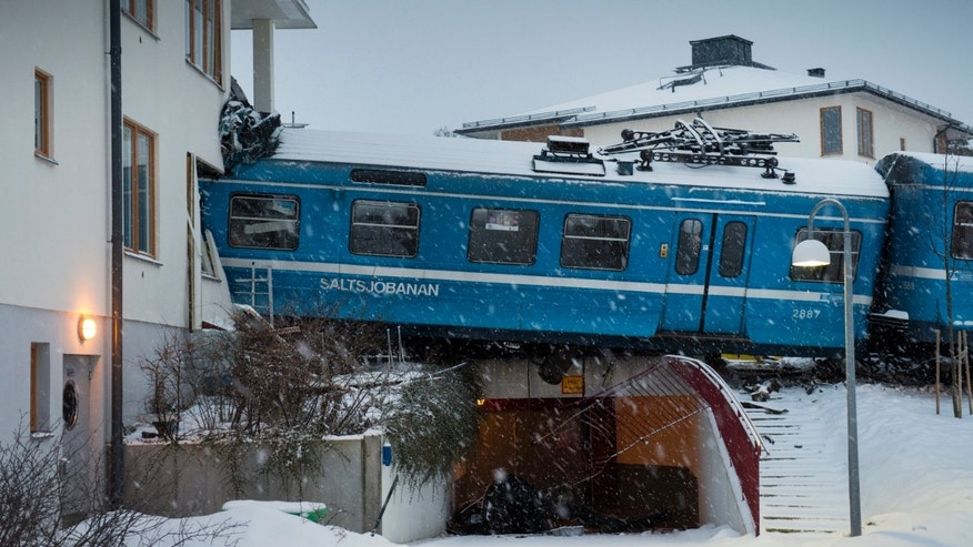 Derailed train that hangs on the edge of the track after it crashed into the side of a  residential building in Saltsjobaden outside Stockholm, Tuesday Jan, 15, 2013. A woman obtained the keys to the train and drove it away before it crashed into the building. The woman was injured in the incident and there are no reports of injuries of people in the building .  (AP Photo/Jonas Ekströmer) **  SWEDEN OUT  **