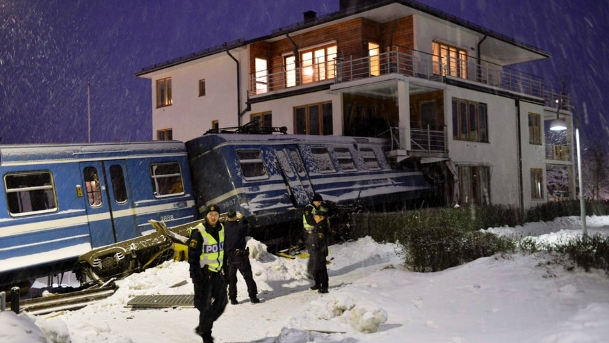 Emergency services attend the scene after a  derailed train crashed into the side of a  residential building in Saltsjobaden outside Stockholm, Tuesday  Jan, 15, 2013. A woman obtained the keys to the train and drove it away before it crashed into the building. The woman was injured in the incident and there are no reports of injuries of people in the building . (AP Photo/Jonas Ekströmer) **  SWEDEN OUT  **