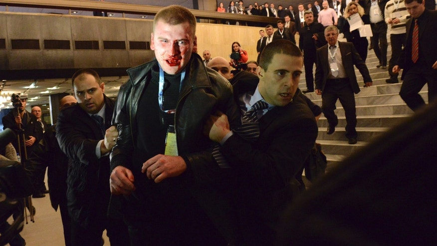 Jan. 19, 2013: An unidentified man (C) is escorted by security personnel after attacking Ahmed Dogan (not pictured), leader of Bulgaria's Movement for Rights and Freedom (MRF) party, while he was delivering his speech during his party's annual conference at the National Palace of Culture in Sofia January 19, 2013.