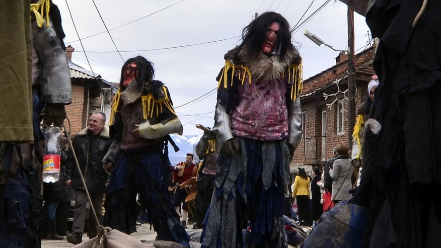 In this picture taken on Sunday, Jan. 13, 2013, villagers masked as cannibals parade during the carnival in Macedonia's southwestern village of Vevcani.  Said to date from pagan times 1,400 years ago, the Vevcani carnival, with its colorful floats and masked revelers, has grown in popularity over the last decade and attracts thousands of visitors for the celebrations on St. Vasilij Day to welcome in the New Year according to the Julian calendar. (AP Photo/Boris Grdanoski)
