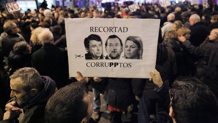 People hold a banner with pictures of Spanish Prime Minister Mariano Rajoy, and Popular Party's members, María Dolores de Cospedal, and Luis Bracenas, ex treasurer,  reading 'let's cut on corrupts'  as they protest against corruption outside the Popular Party's headquarters in central Madrid, Friday, Jan. 18, 2013. A former Spanish ruling party treasurer amassed 22 million euro ($29 million) in Swiss bank accounts, a court said, prompting a barrage of questions Friday about whether senior officials may have been involved in alleged corruption before taking power in 2011. (AP Photo/Andres Kudacki)