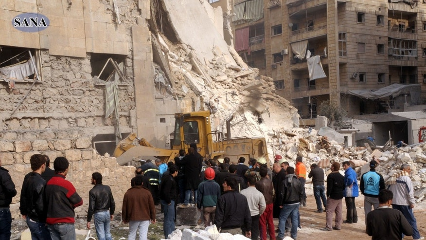 This photo released by the Syrian official news agency, SANA, shows rescue workers and bystanders at a building damaged by a rocket attack, that killed at least 12 people, in Aleppo, Syria, Friday, Jan. 18, 2013.  In a spike in civil war violence that Syrian state media blamed on rebel fighters a rocket attack in the northern city of Aleppo occurred during a particularly bloody week nearly two years after an uprising began against Assad's regime. (AP Photo/SANA)