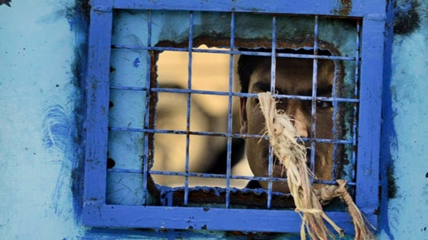 In this Monday, April 25, 2011 file photo, a prisoner looks out of his cell window at the main prison in Kandahar, Afghanistan. The United Nations said Sunday that Afghan authorities were still torturing prisoners, such as hanging them by their wrists and beating them with cables.