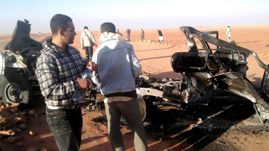 "In this undated photo, men look at the wreckage of a vehicle near Ain Amenas, Algeria. Algerian bomb squads scouring a gas plant where Islamist militants took dozens of foreign workers hostage found ""numerous"" new bodies on Sunday, Jan. 20, 2013 as they searched for explosive traps left behind by the attackers, a security official said, a day after a bloody raid ended the four-day siege of the remote desert refinery. (AP Photo/Echorouk Elyaoumi)"