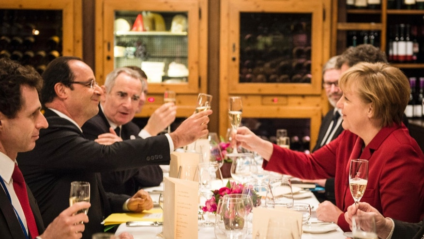 German Chancellor Angela Merkel, right, and French President Francois Hollande toast during a private dinner in a restaurant in Berlin Monday, Jan. 21, 2013. Germany and France mark 50 years since they signed the Elysee Treaty, a post-war friendship pact. On Tuesday, Jan 22 the politicians mark the diplomatic milestone. (AP Photo/Bundesregierung, Jesco Denzel)