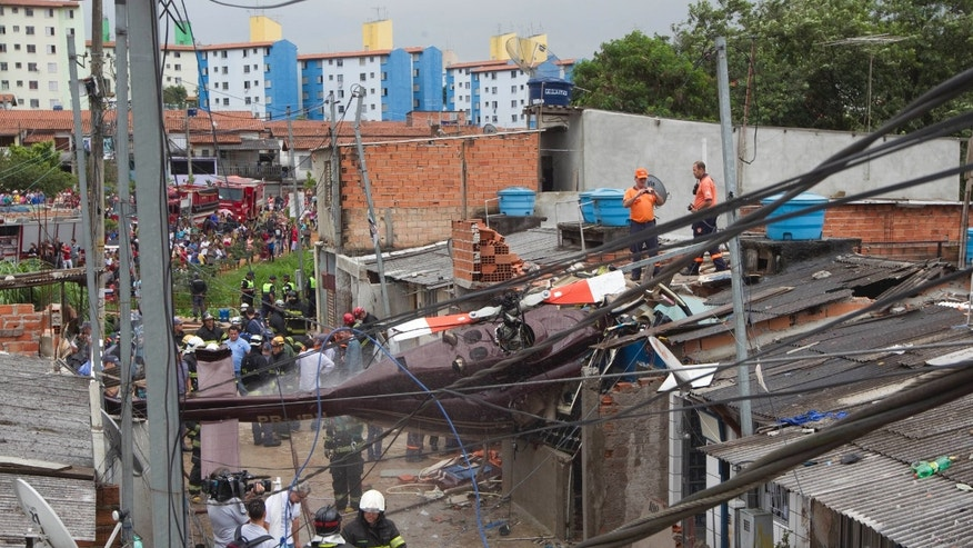 Firefighters work at the site where a helicopter crashed into a residential area of Sao Paulo, Brazil, Monday, Jan. 21, 2013. According to authorities, the pilot flying the private helicopter died, and three passengers were injured. (AP Photo/Andre Penner)