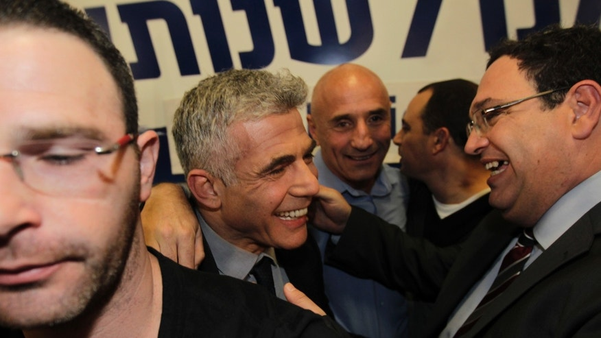 "Yair Lapid celebrates with members of  his ""Yesh Atid"" party in Tel-Aviv, early Wednesday, Jan. 23, 2013.  The party, formed just over a year ago, out did forecasts by far and are predicted to capture as many as 19 seats, becoming parliament's second-largest party, after Netanyahu's Likud-Beiteinu bloc, which won 31, according to the exit polls. (AP Photo/Sebastian Scheiner)"