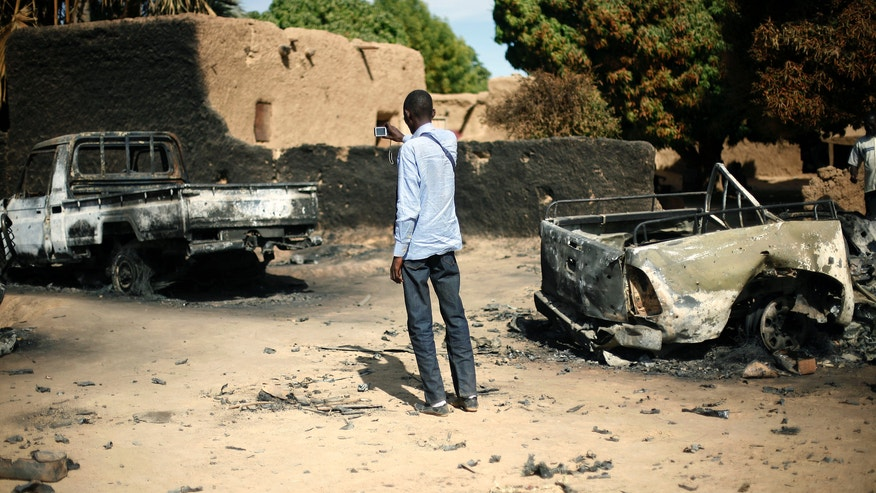 An unidentified man takes a picture of  the charred  remains of  trucks used by radical Islamists on the outskirt of Diabaly, Mali,  some  460kms (320 miles) North of the capital Bamako Monday Jan. 21, 2013.  French and Malian troops took control Monday of the town of Diabaly, patrolling the streets in armored personnel carriers and inspecting the charred remains of a pickup truck with a mounted machine gun left behind by the fleeing militants. (AP Photo/Jerome Delay)