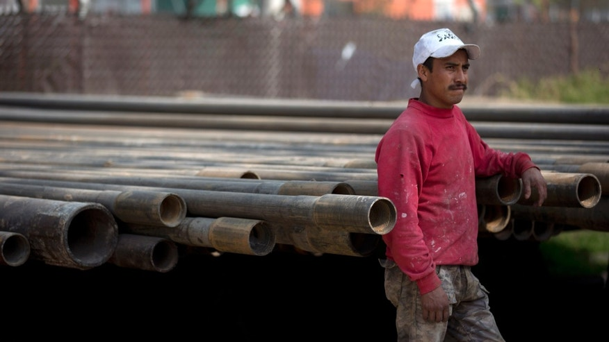 A city worker stands next to large tubes as he watches a ceremony unveiling an exploratory well into a recently found aquifer in Mexico City, Wednesday, Jan. 23, 2013. City authorities announced the discovery of an aquifer more than a mile below ground that could provide enough water for at least some of the metropolitan area's 20 million residents but warned that many feasibility studies remain to be done. (AP Photo/Dario Lopez-Mills)