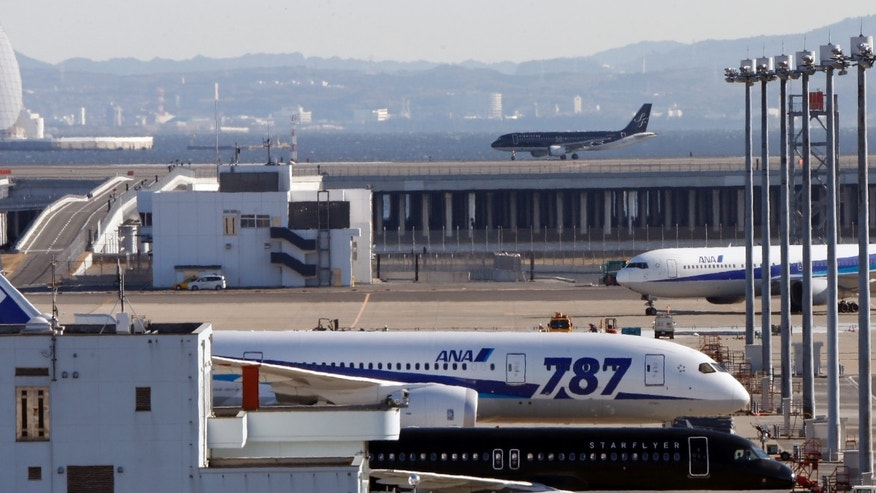 In this Friday, Jan. 18, 2013 photo, a grounded All Nippon Airways' Boeing 787 is parked on the tarmac at Haneda airport in Tokyo. Japan's transport safety agency says a lithium ion battery on a Boeing 787 that overheated during an All Nippon Airways flight earlier this month, prompting an emergency landing, was not overcharged. (AP Photo/Koji Sasahara)
