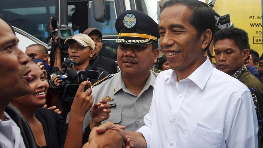 In this photo taken on Jan. 3, 2013, Jakarta Gov. Joko Widodo, right, is greeted by his supporter during his inspection of bus transportation in Jakarta, Indonesia. Widodo's trip through his inundated city of 14 million reflected his hands-on approach to leadership, a style that helped him win election in September against an incumbent who was backed by the establishment political parties. His traffic plans include more buses to ply the city's dedicated lanes, some of which have already arrived, more roads and a scheme that would restrict the amount of cars that travel into the city center each day based on whether their license plate ends in odd or even number. (AP Photo/Achmad Ibrahim)