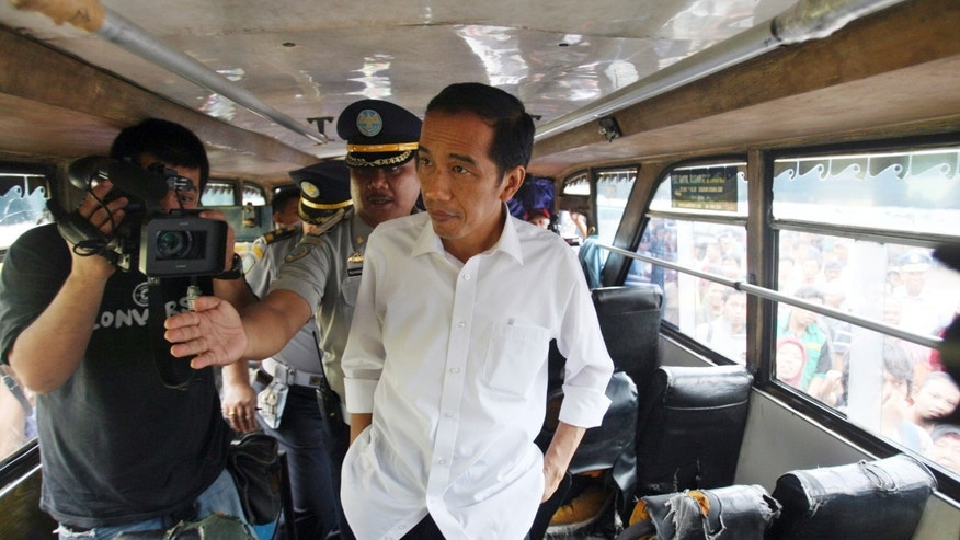 In this photo taken on Jan. 3, 2013, Jakarta Gov.  Joko Widodo inspects a bus at Terminal Senen in Jakarta, Indonesia. Widodo's trip through his inundated city of 14 million reflected his hands-on approach to leadership, a style that helped him win election in September against an incumbent who was backed by the establishment political parties. His traffic plans include more buses to ply the city's dedicated lanes, some of which have already arrived, more roads and a scheme that would restrict the amount of cars that travel into the city center each day based on whether their license plate ends in odd or even number. (AP Photo/Achmad Ibrahim)