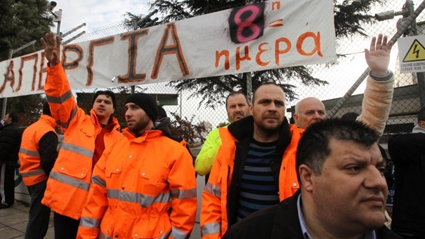 "Jan. 24, 2013: Striking metro workers stand under a banner that reads: ""Strike 8th Day"" at the the central depot in Athens."