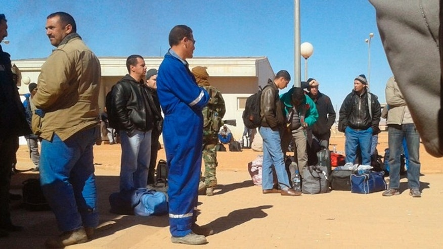Jan. 16, 2013: In this photo secretly taken by a hostage held at the In Amenas gas complex, an Islamic militant dressed in camouflage stands among Algerian employees.