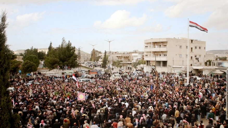 In this Wednesday, Jan. 23, 2013 photo released by the Syrian official news agency SANA, Syrians take part in a funeral procession for those killed in a car bomb explosion at a headquarters of a pro-government militia late Monday in the central town of Salamiya in Hama province, Syria. The Observatory said on Tuesday that at least 42 people were killed in the car bomb attack in the Salamiya blast. The Syrian government rarely comments on regime casualties in the nearly two years of fighting. (AP Photo/SANA)