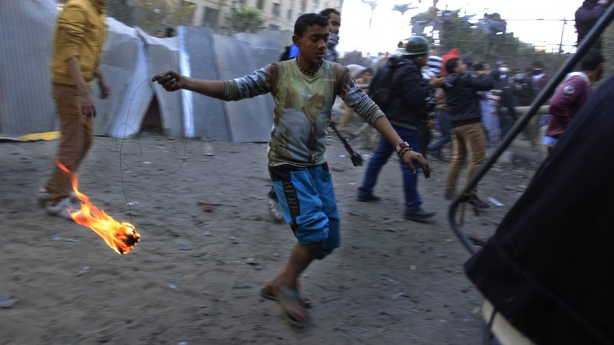 Jan. 25, 2013 - Egyptian protesters clash with riot police, not seen, near Tahrir Square, Cairo, Egypt.