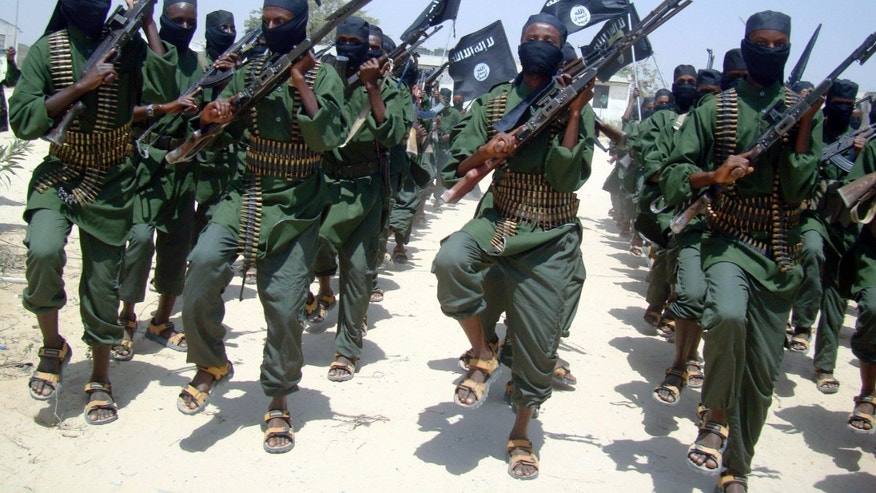 FILE - In this Thursday, Feb. 17, 2011 file photo, al-Shabab fighters march with their weapons during military exercises on the outskirts of Mogadishu, Somalia. Twitter suspended the account used by the Somali militants on Friday, Jan. 25, 2013, after the insurgents used the micro-blogging site to post a hostage video and death threat. (AP Photo/Mohamed Sheikh Nor, File)