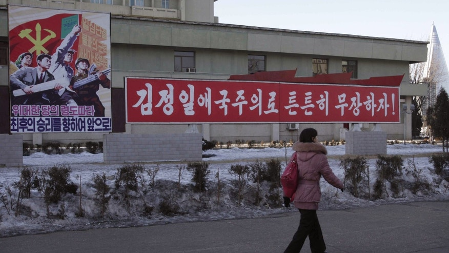 "A woman walks by a board which reads ""Forward to Final Victory under Leadership of Great Party,"" left, and another reads reads ""Let's firmly arm ourselves with the patriotism of Kim Jong Il,"" in Changgwang Street, Pothonggang District of Pyongyang, North Korea, Friday Jan, 25, 2013. Following new U.N. sanctions punishing North Korea for a December rocket launch, North Korea warned that it would continue launching long-range rockets and conduct a nuclear test. (AP Photo/Kim Kwang Hyon)"