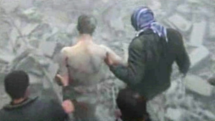 In this image taken from video obtained from Bambuser, which has been authenticated based on its contents and other AP reporting, men help an injured and heavily bleeding man through the rubble of a building that was destroyed following what activists said were two airstrikes in the Arbeen neighborhood of Damascus, Syria, Friday, Jan. 25, 2013. (AP Photo/Bambuser via AP video)