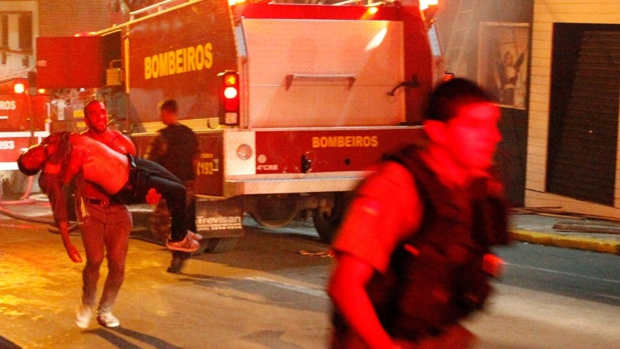 A man carries an injured man, victim of a fire at the Kiss  club in Santa Maria city,  Rio Grande do Sul state, Brazil, early Sunday, Jan. 27, 2013.  (AP Photo/Agencia RBS)