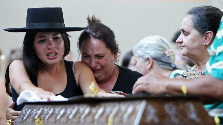 Jan. 27, 2013: Relatives cry next to a coffin at a gymnasium where bodies were brought for identification in Santa Maria city, Rio Grande do Sul state, Brazil.