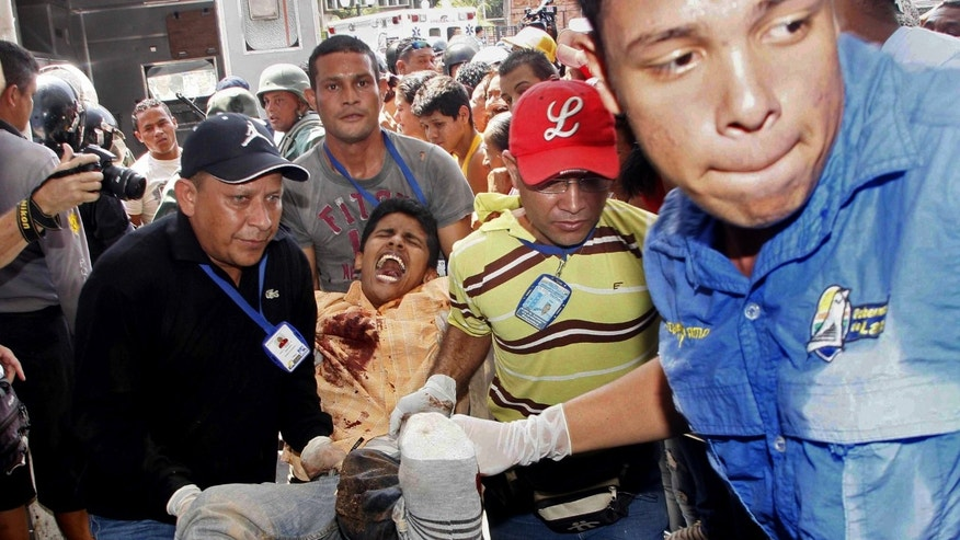 Jan. 25, 2013: An injured prison inmate is carried into the hospital in Barquisimeto, Venezuela.