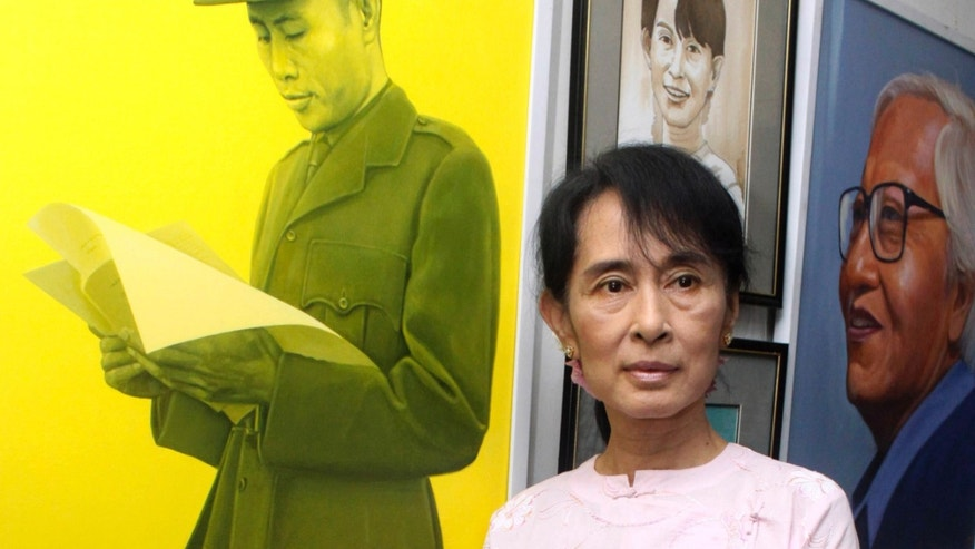 In this photo taken on Oct. 23, 2011, Myanmar pro-democracy leader Aung San Suu Kyi poses by a painting of her father, Gen. Aung San, left, during an art exhibition at her National League for Democracy party headquarters in Yangon, Myanmar. Suu Kyi is scheduled to meet South Korean President Park Geun-hye on Tuesday, Jan. 29, 2013 during her five-day trip. The meeting between two of the most prominent woman figures in Asia spotlights a tragic coincidence in their family history: Suu Kyi's father, Gen. Aung San, was killed by a group of assassins in 1947 while Park's, President Park Chung-hee, was assassinated by his intelligence chief in 1979. (AP Photo/Khin Maung Win)