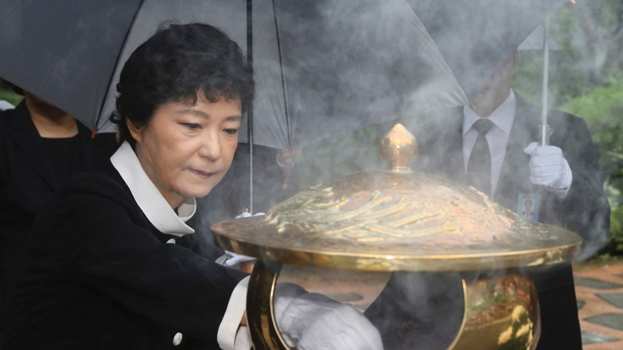 FILE - In this  Aug. 21, 2012 file photo, Park Geun-hye, then-presidential candidate of the ruling Saenuri Party, burns incense in front of the tomb of her father and former authoritarian President Park Chung-hee at the National Cemetery in Seoul, South Korea. Park is scheduled to meet Myanmar pro-democracy leader Aung San Suu Kyi on Tuesday, Jan. 29, 2013, during Suu Kyi's five-day visit to South Korea. The meeting between two of the most prominent woman figures in Asia spotlights a tragic coincidence in their family history: Suu Kyi's father, Gen. Aung San, was killed by a group of assassins in 1947 while Park's, President Park Chung-hee, was assassinated by his intelligence chief in 1979. (AP Photo/Newsis, File)  KOREA OUT
