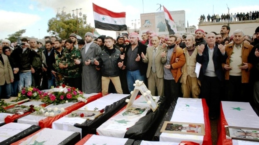 Jan. 23, 2013: In this photo released by the Syrian official news agency SANA, Syrians take part in a funeral procession for those killed in a car bomb explosion at a headquarters of a pro-government militia late Monday in the central town of Salamiya in Hama province, Syria.