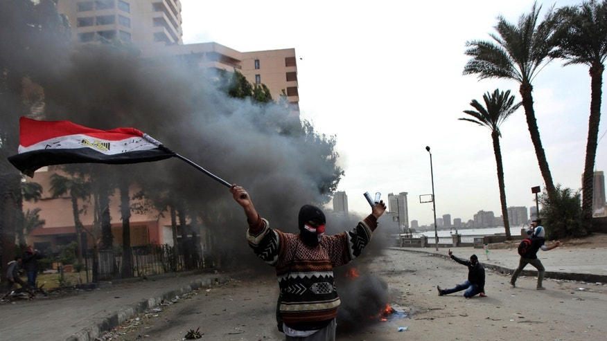 A protester part of the Black Bloc, holds the Egyptian national flag during clashes with riot police near Tahrir Square, Cairo, Egypt, Monday, Jan. 28, 2013. An unpredictable new element has entered Egypt's wave of political unrest, a mysterious group of black-masked young men calling themselves the Black Bloc. They present themselves as the defenders of protesters against the rule of President Mohammed Morsi, but Islamists have used them to depict the opposition as a violent force wrecking the nation. (AP Photo/Khalil Hamra)