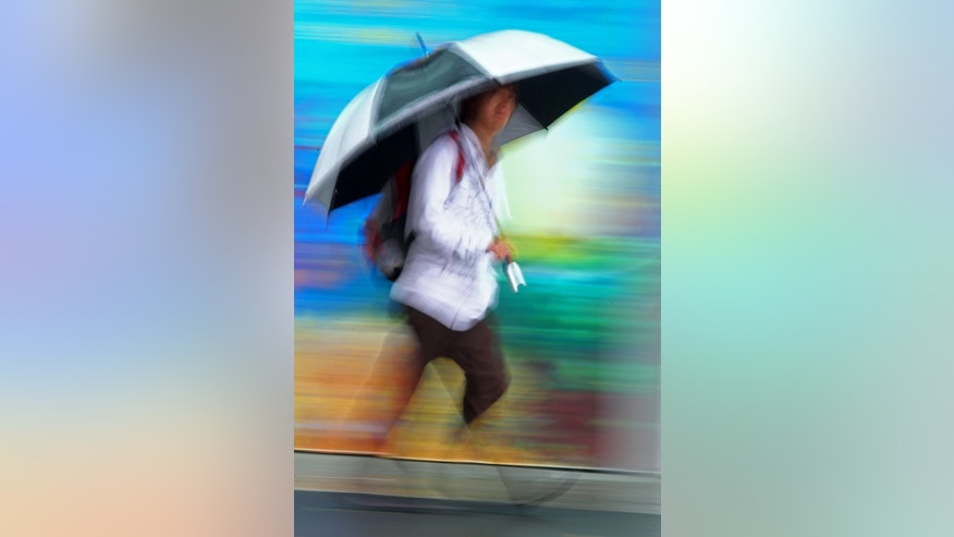 In this image made with a slow shutter speed, a man uses an umbrella to fend off the rain as he walks on a street in Sydney, Australia, Monday, Jan. 28, 2013. Torrential rain over the weekend flooded several towns in eastern Australia, and three deaths were reported. (AP Photo/Rick Rycroft)