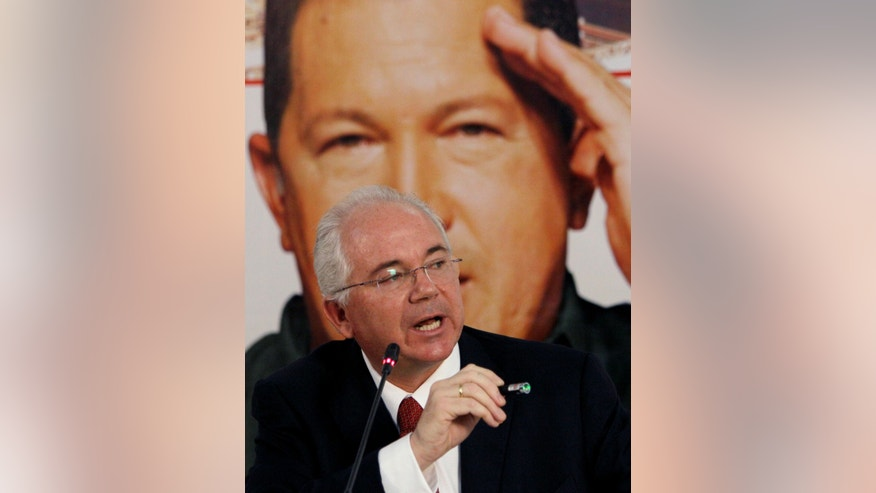 Venezuela's Oil Minister Rafael Ramirez gives a news conference at his office where a picture of Venezuela's President Hugo Chavez hangs behind him in Caracas, Venezuela, Monday, Jan. 28, 2013. Chavez remains in Cuba after his fourth surgery for cancer. (AP Photo/Fernando Llano)