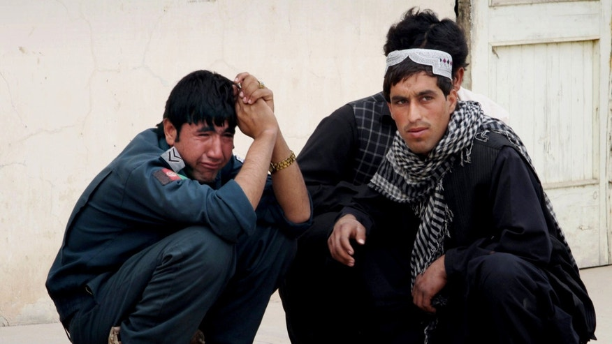 An Afghan policeman, left, mourns after a police truck was hit by a roadside bomb in Kandahar, south of Kabul, Afghanistan, Sunday, Jan. 27, 2013. A police truck packed with officers and detainees struck a roadside bomb in southern Afghanistan's largest city, killing several of those aboard, officials said Sunday. (AP Photo/Allauddin Khan)