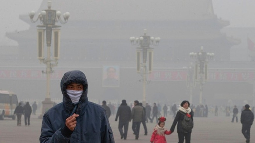 Jan. 29, 2013: A man wears a mask on Tiananmen Square in thick haze in Beijing.