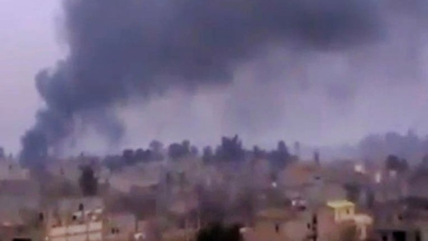 Jan. 28, 2013: In this image taken from video obtained from the Ugarit News, which has been authenticated based on its contents and other AP reporting, Smoke rises from heavy shelling in Deir el-Zour, Syria.