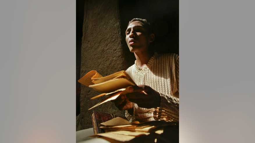 Mar. 16, 2004: Alhousseini Ould Alfadrou, 16, sings verses from crumbling ancient Islamic manuscripts in a mud-walled house in Timbuktu, Mali.